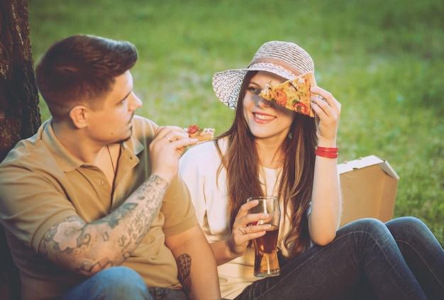 公園でのピクニックに幸せなカップル。ピザを食べてビールを飲む