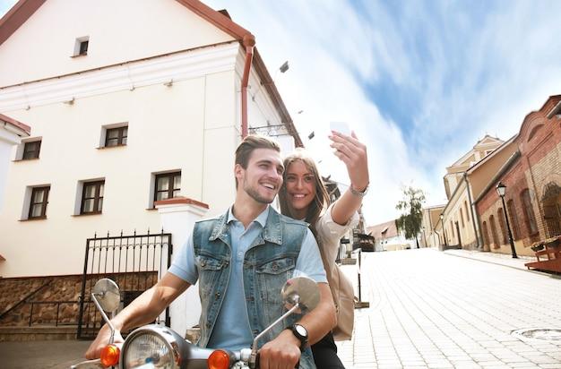야외에서 스마트폰으로 셀카 사진을 만드는 스쿠터에 행복한 커플