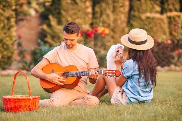 夏のピクニックで幸せなカップル。男はギターを弾き、女は白い子犬と