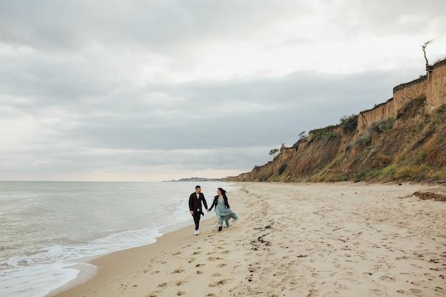 海で素晴らしい一日を楽しんでいるビーチで幸せなカップル。