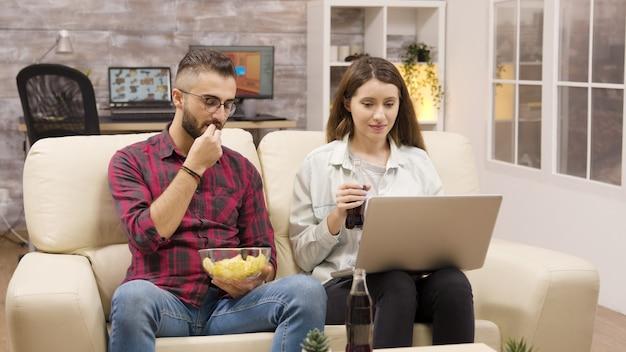 ソファでチップを食べてラップトップを見て幸せなカップル