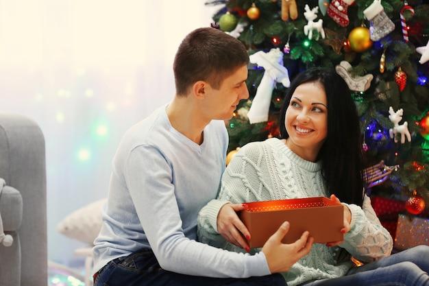 Счастливая пара на полу с подарками в украшенной рождественской комнате