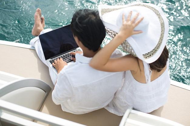 노트북으로 요트에 행복 한 커플