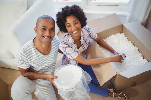 Happy couple opening boxes in the living room