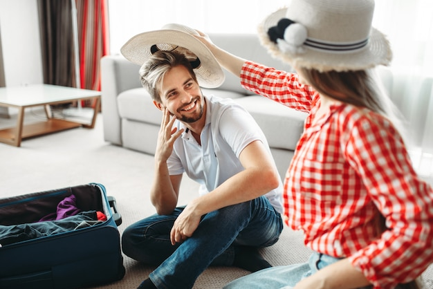 幸せなカップルが休暇のためにバッグを梱包