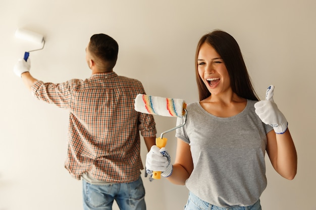 Счастливая пара красит стену валиком