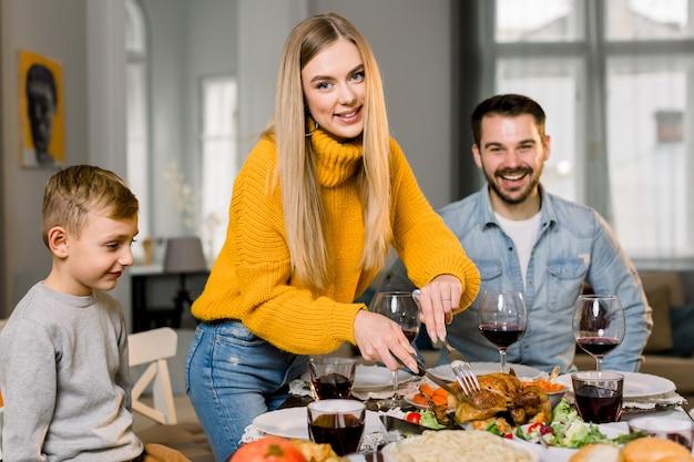 행복한 커플 부모와 그들의 작은 아들 축제 테이블에 앉아 구운 칠면조를 먹을 것입니다. 어머니가 칠면조를 절단하는 동안 집에서 함께 맛있는 저녁 식사를하는 행복한 가족
