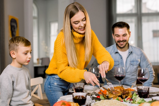 Happy couple parents and their little son sitting at festive table and going to eat roasted turkey. happy family having delicious dinner together at home while mother cutting turkey