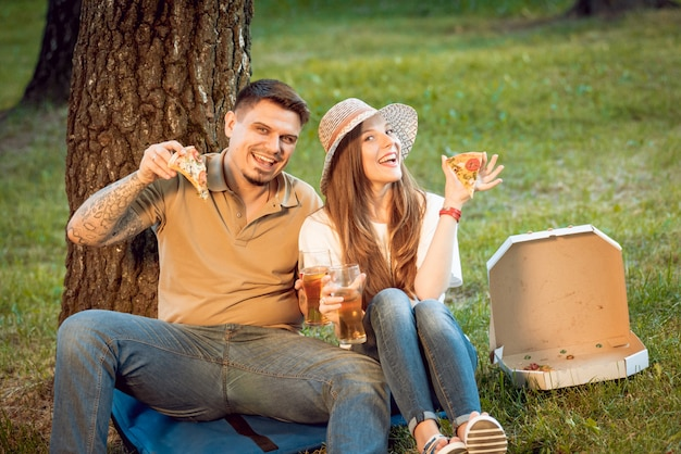 Happy couple on picnic in the park. eating pizza and drinking beer