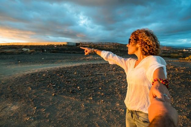 幸せなカップルは、夕日の光の中で屋外でレジャー活動を楽しんでいます-休暇中の観光客は、愛と友情を持って手をつないで一緒に楽しんでいます