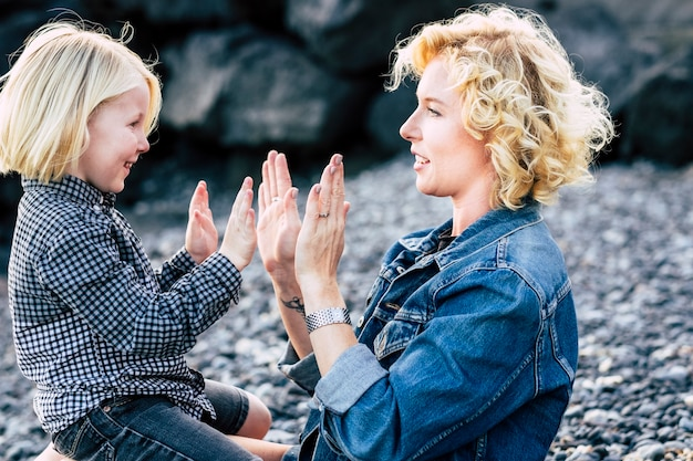 Happy couple playful anmd smiling together mother and son in outdoor happy leisure activity. forever concept, hands play growing up a children. laugh and have fun caucasian family people. blonde boy a