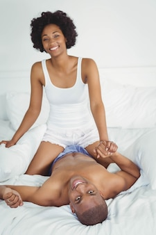 Happy couple playing on the bed at home