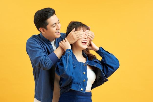 숨바꼭질을 하는 행복한 커플, 아내 뒤에 서서 눈을 감고 노란색 배경을 가진 아프리카 남자.