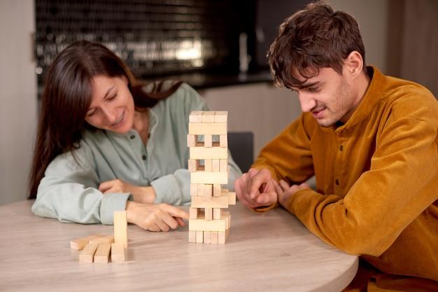Счастливая пара, играя, чтобы построить башню, сидя на кухне дома и весело проводя время вместе