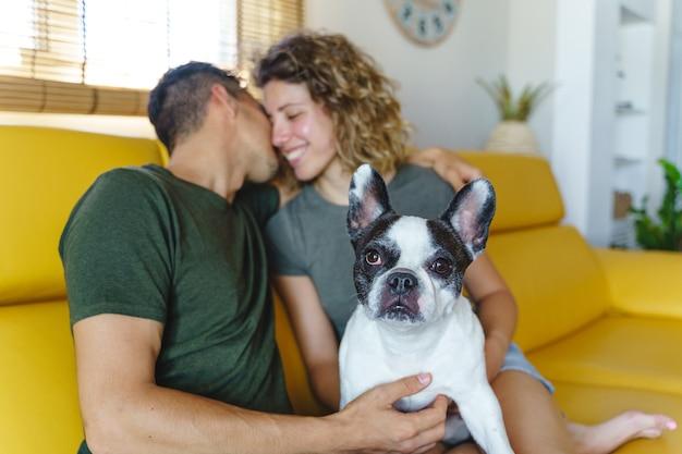 家で犬と遊ぶ幸せなカップル。ソファの上のブルドッグペットと恋にカップルの水平方向のビュー。