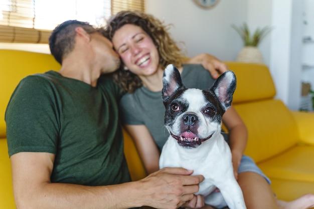 家で犬と遊ぶ幸せなカップル。ソファの上でブルドッグペットと笑っているカップルの水平方向のビュー。