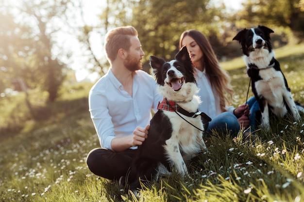야외 공원에서 강아지와 함께 노는 행복 한 커플. 사람, 애완 동물 개념