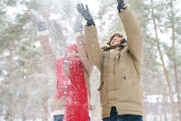 Счастливая пара играет со снегом