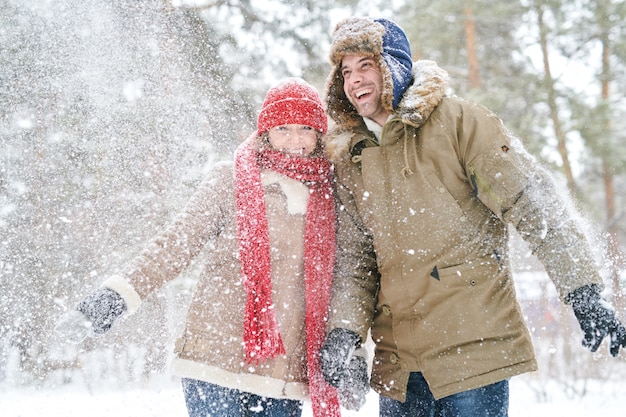 Happy couple playing with snow