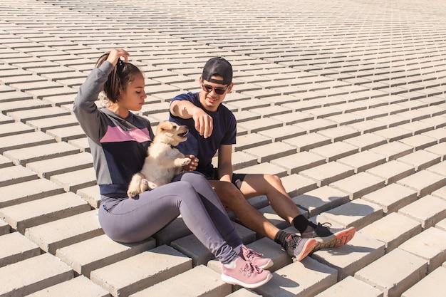 海岸で子犬と遊んで幸せなカップル。