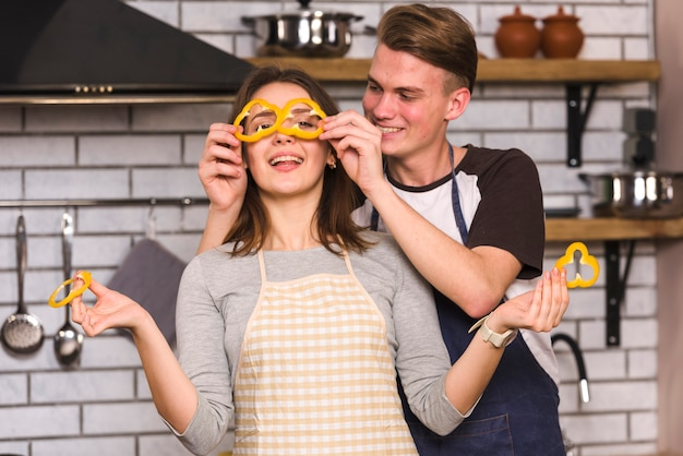 Happy couple playing with vegetables in kitchen
