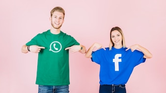 Happy couple pointing at their t-shirt with facebook and whatsapp icon