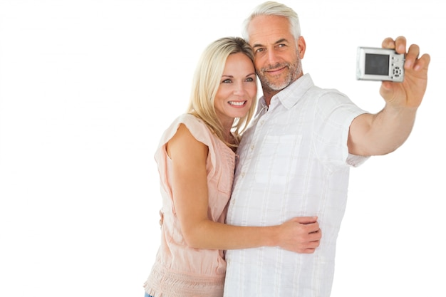Happy couple posing for a selfie on white background