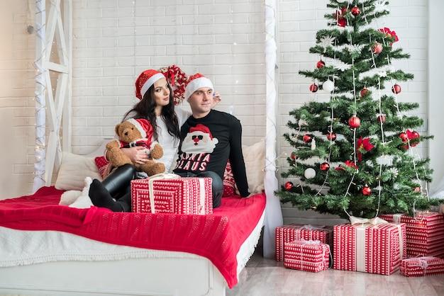 スタジオのベッドに座ってポーズをとって幸せなカップル