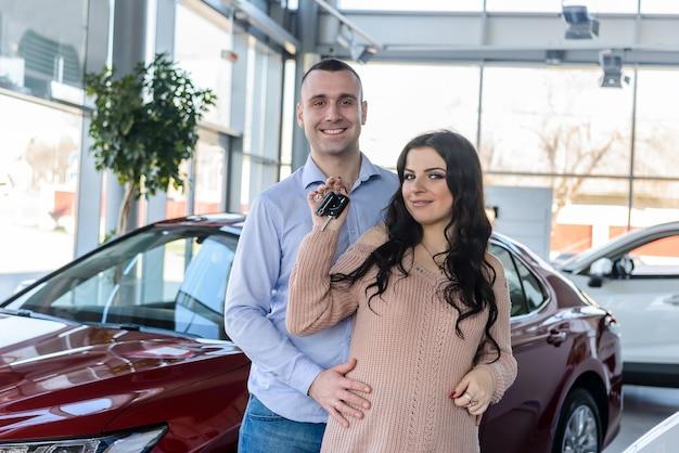 新しい車の鍵でポーズをとって幸せなカップル
