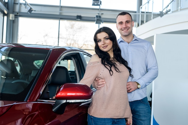 Happy couple posing with new cars in showroom