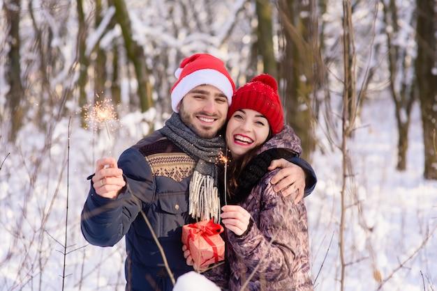 幸せなカップルが赤い帽子、冬の公園でベンガルズでポーズ