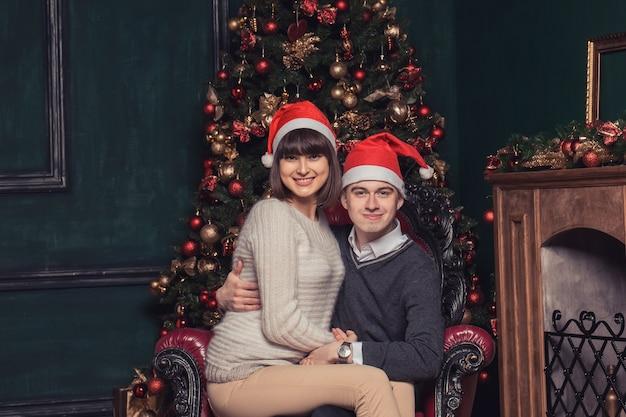 クリスマスツリーの横にサンタの帽子でポーズをとって幸せなカップル