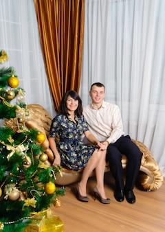 Счастливая пара позирует с елкой