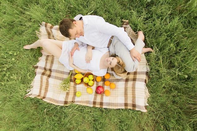 행복 한 커플 임신 한 여자와 그녀의 남편은 잔디에 피크닉 담요에 누워.