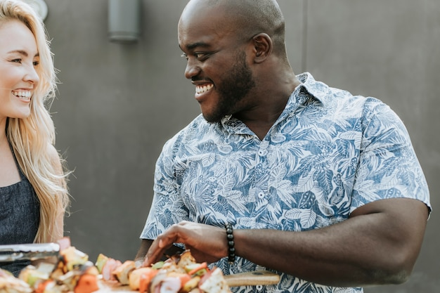 Happy couple preparing barbeque skewers