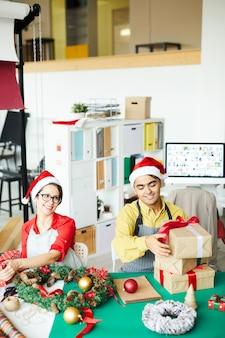 Coppie felici che preparano i regali e le decorazioni di natale