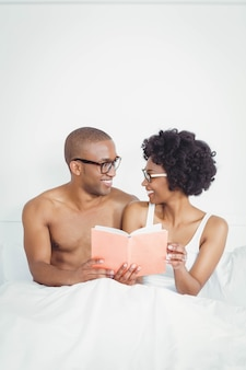 Happy couple reading a book together on the bed