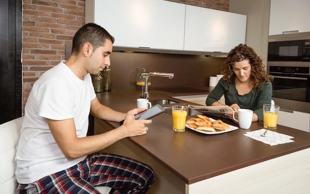 家の朝食でニュースを読んで幸せなカップル