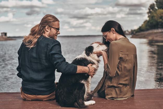 Счастливая пара. вид сзади красивой молодой пары, играющей с собакой, сидя у озера на открытом воздухе