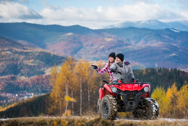 Happy couple on red quad bike riding in the mountains.