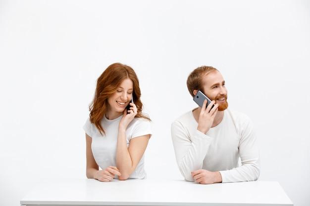携帯電話を話して幸せなカップル赤毛