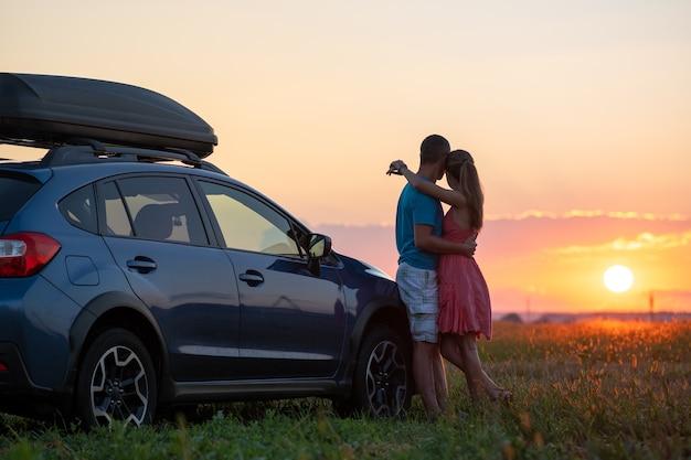 일몰에 신혼 여행을 하는 동안 그들의 suv 차 옆에서 휴식을 취하는 행복한 커플.