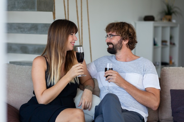 행복 한 커플 휴식, 와인을 마시고 소파에 앉아있는 동안 이야기. 집에서 낭만적 인 순간.