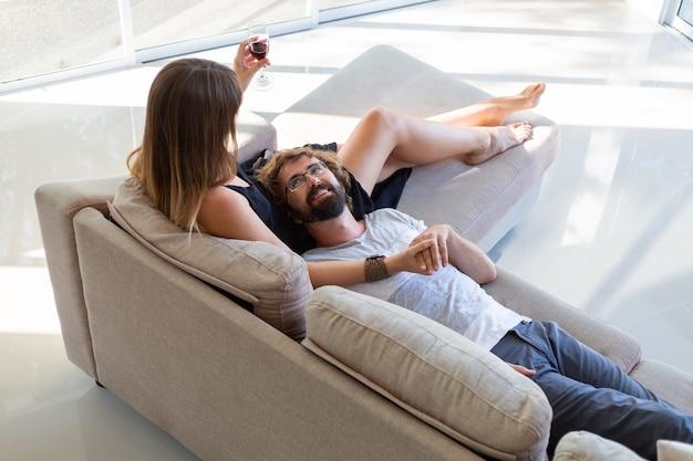 リラックスして、ワインを飲み、ソファに座って話している幸せなカップル。家でロマンチックな瞬間。