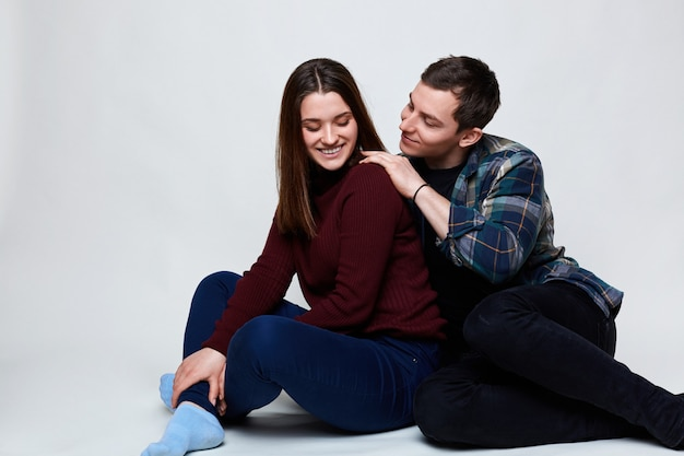 Happy couple relaxing on white floor. handsome guy wearing checked shirt touching his pretty girlfriend dressed in jeans and red sweater having smile being happy to be near her lover