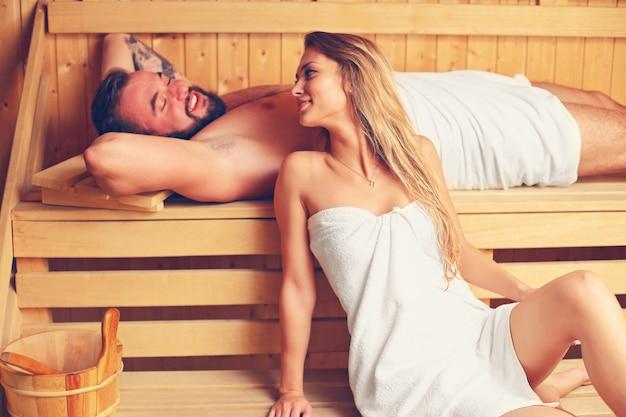 Happy couple relaxing in wooden sauna