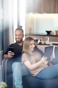 ガジェットを手に家で休んでいる幸せなカップル、彼らはビデオを見たり、メッセージを読んでいます