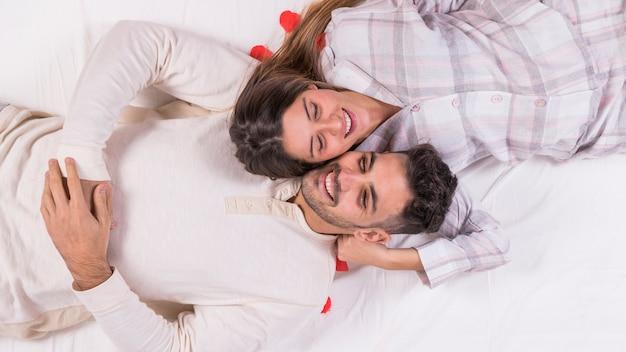 幸せなカップルがベッドで休んで