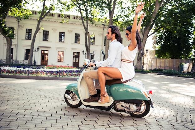 Счастливая пара, едущая на скутере