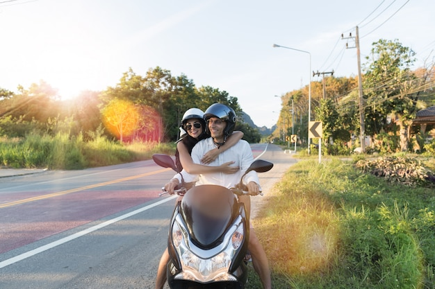 Happy couple riding motorcycle in countryside excited woman and man travel on motorbike road trip